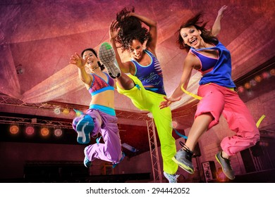 young women in sport dress jumping at an aerobic exercise