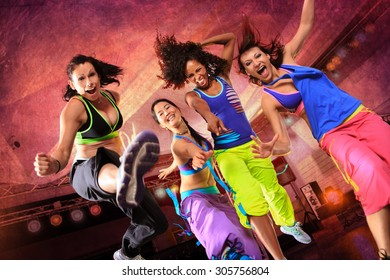 young women in sport dress jumping at an aerobic or fitness exercise
