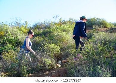 Young women sporty hiker climbing on the Black Mountain in San Diego, California, USA. Women hikers going up of the mountain during blue sunny day. 01/22/2019