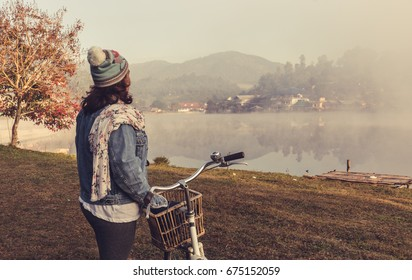 young women stand by the bike in the morning beside the lake, with a rustic village in the background. The travel of Asian women  are exhausted from work and then feel the nature help relax in winter.