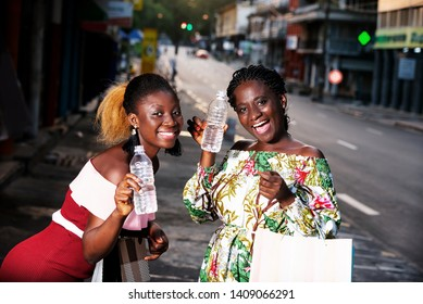 Young women standing outdoors looking at the camera smiling with bottles of water in hand after shopping.