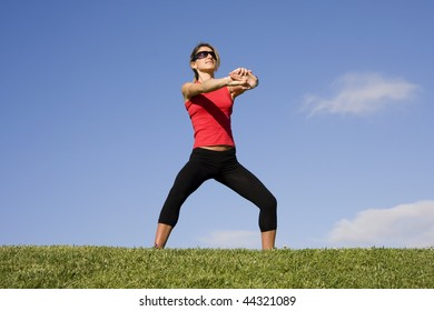 Young women stretching her arms isolated on a blue sky
