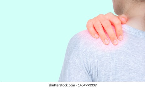 Young women suffering from shoulder pain injury and holding her hand on trapezius muscle. Office syndrome, healthcare and medical concepts. Isolated on blue pastel background with clipping path.