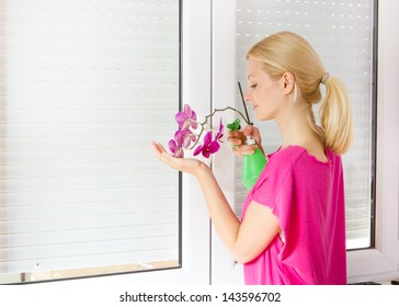 Young women take care of the flower of orchid.