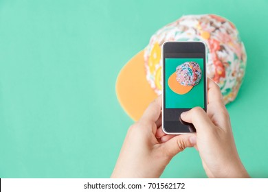 young women taking photo to hat with cell telephone or smartphone digital camera for Post to sell Online on the Internet . Customise pastel bright colors tone .