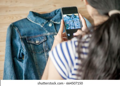 young Women taking photo to shirts with cell telephone or smartphone digital camera for Post to sell Online on the Internet .