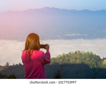 young women taking picture by cell phone in morning