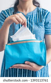 Young women taking sanitary napkins inside of her cosmetic bag on blue background