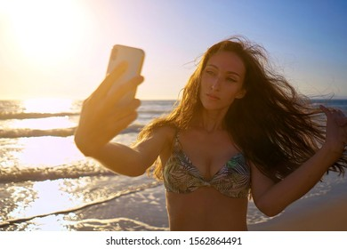 Young women taking selfie photo using smartphone camera and having fun on the sunset beach