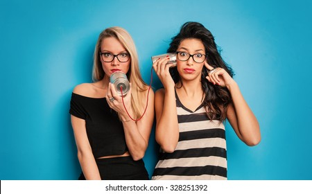 Young women talking with tin can telephone against blue background. Conceptual funny image for communication.