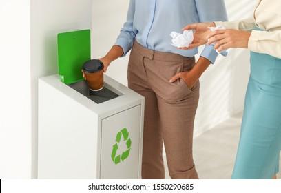 Young women throwing garbage into recycling bin in office, closeup