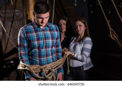 Young women tie a young sad guy to a column on the deck of a ship, escape the room game concept