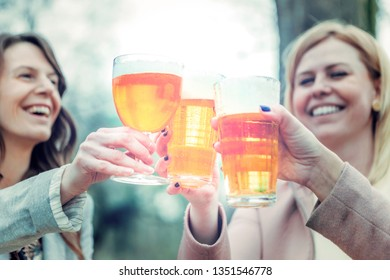 young women toasting with beer, celebrating life outdoor. Friendship, togetherness, positive emotion concept.