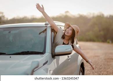 Young women, tourists, enjoy traveling and raise their hands to express freedom. Happy on the car....