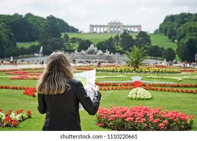 Young Women Tourists Expand survey map in Gloriette in the Schönbrunn garden, Vienna, Austria