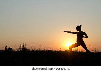Young women training karate on sunset.