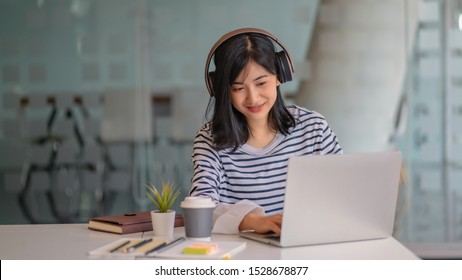Young women using laptop and listening song in on-ear headphones.