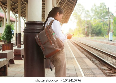 Young women waiting on station platform with backpack. concept travel, color of vintage tone and soft focus.