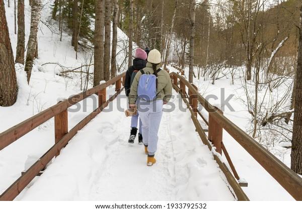 young-women-walk-along-wooden-600w-19337