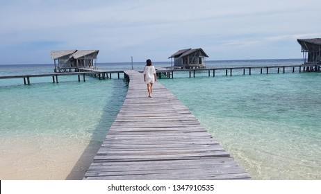 Young women walk on cottage bridges in Pulo Cinta Gorontalo Indonesia resorts