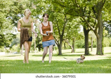 Young women walking dog at a park