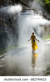 A young women walking with her arms spread in the mist of a public water mister installed on the wharf of the river Seine in the center of Paris.