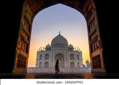 Young women walking into the Taj Mahal world wonder at sunrise
