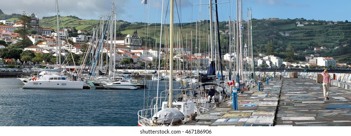 Young women is walking at the pier of the Marina in Horta (Faial Island, Azores)