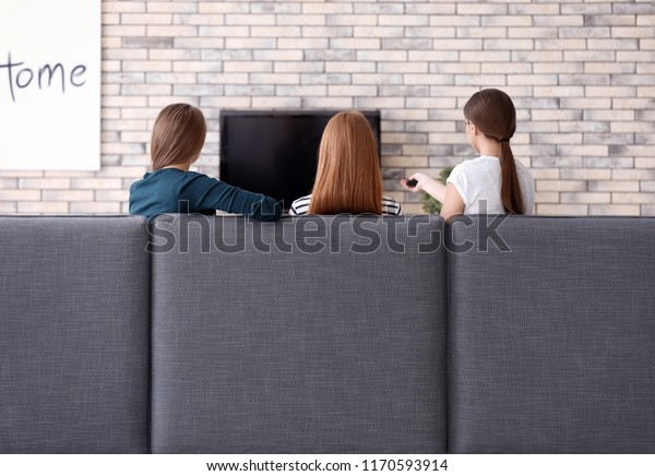 Young women watching TV at home