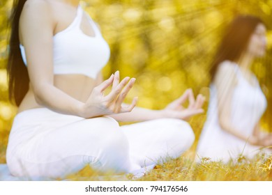 Young Women wear white sportswear. Being meditated on yoga is in the garden. Make good health. Close up of beautiful hands. copy space