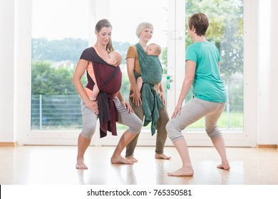 Young women wearing babies for mother-child bonding and doing pelvis floor exercises