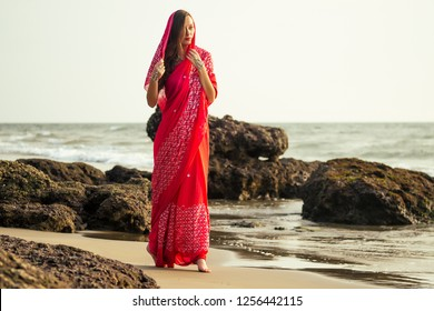 Young women wearing a red saree on the beach goa India.girl in traditional indian sari on the shore of a paradise island among the rocks and sand enjoying the freedom and the sunset