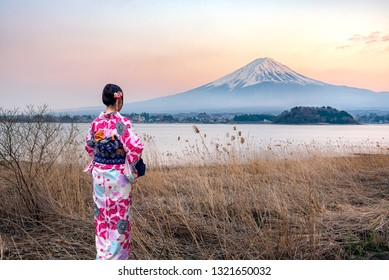 Young women wearing traditional Japanese Kimono with Mt. Fuji and lake Kawaguchi in the afternoon sunset.