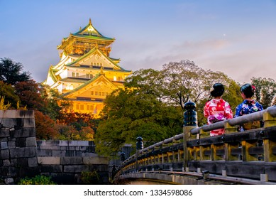 Young women wearing traditional Japanese Kimono with Osaka Castle in Osaka with autumn leaves landmark of Unesco, Japan.