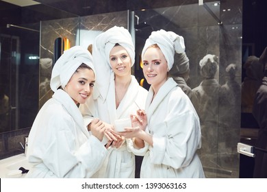 Young women in white bathrobe in bathroom at a spa party