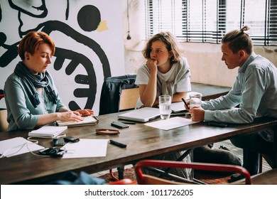 Young women working and communicating together in creative office. Successful feminine teamwork and business brainstorm concept.