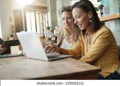 Young women working on laptop in coffeeshop