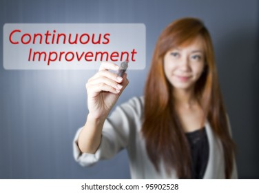 Young women write Continuous Improvement word.