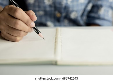 young women writing on blank notebook by black pencil
