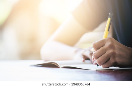 A young women writing on the notbook in the morning.
