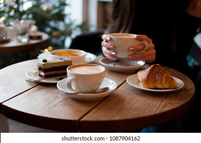Young women's hands holding a cup of coffee in a cafe