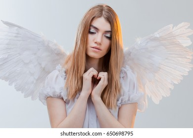 Young and wonderful blonde girl in the image of an angel with white wings.