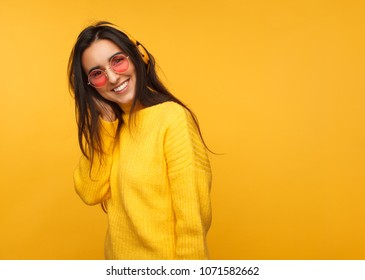 Young wonderful girl in yellow sweater wearing headphones and sunglasses smiling at camera.