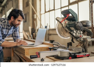 Young woodworker working online with a laptop while leaning on bench by a mitre saw in his workshop