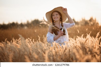 Young wooman in hat summer evening in the field