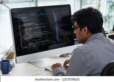 Young IT worker concentrating on his work, he sitting at the table and looking at monitor at office