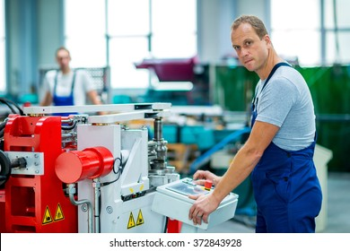 young worker in factory using machine