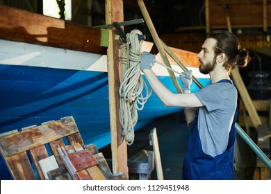 Young worker in gloves and overalls preparing ropes for further shipbuilding work