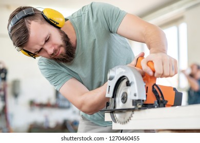 young worker with hand saw in a carpenter's workshop