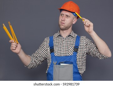 Young worker in helmet holds pencil and ruler against gray background